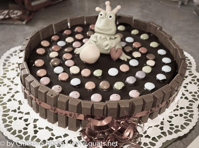Bunter Kinderkuchen umringt von KitKat, dekoriert mit Smarties und einem grünen Froschkönig aus Marzipan